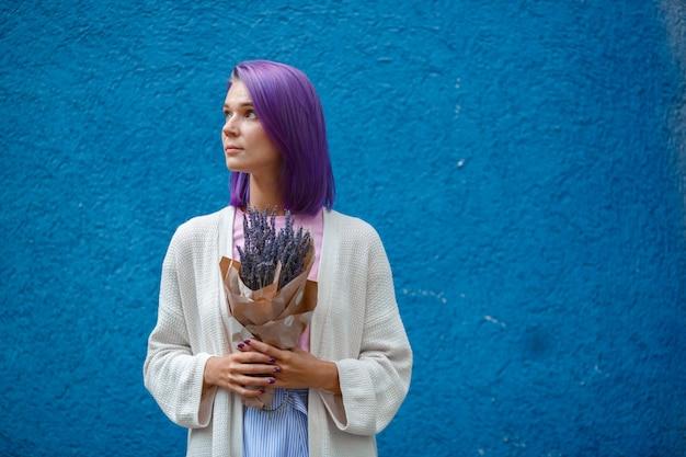 紫色の髪の少女は、ラベンダーの花束を保持しています