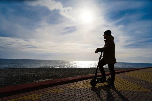 日没、シルエット、空き領域でスクーターの男