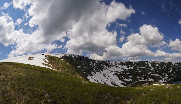 Сугробы лежат на склоне горы в алтайских горах