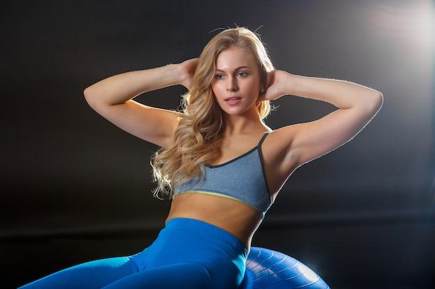 運動ボールでトレーニングフィットネス服の若い女性