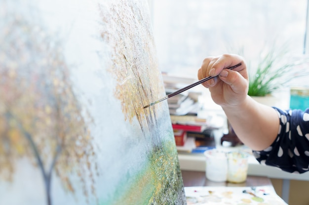 アーティストの手が油絵をクローズアップで描く
