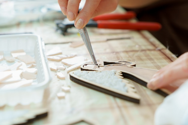 女性の手のアーティストがモザイクをクローズアップ収集