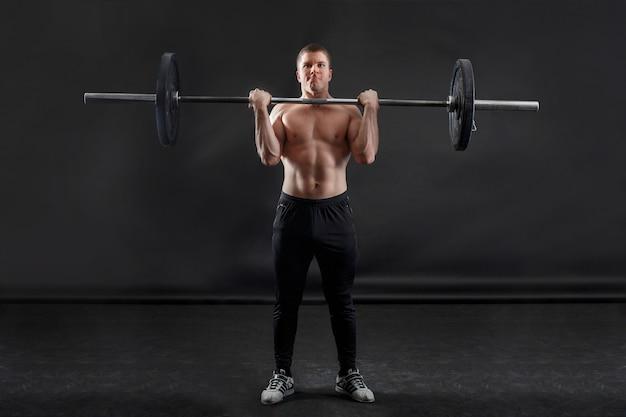 筋肉ボディービルダーは彼の肩に重い体操バーベルを保持しています。