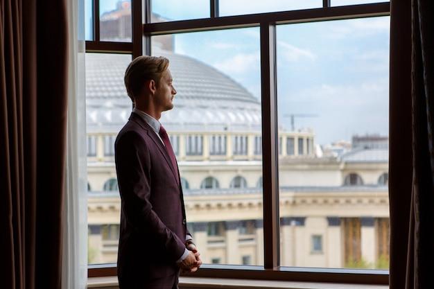 Бизнесмен стоит и смотрит в окно на городской пейзаж