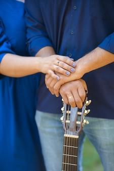 Крупным планом женщина обнимает мужчину с гитарой в руках