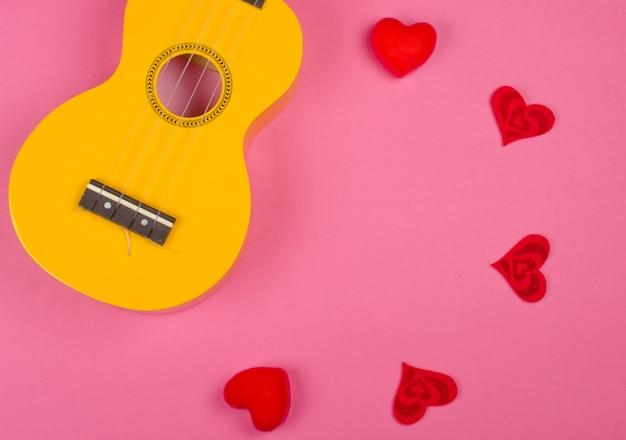 ウクレレギターと明るいピンクの背景(愛の歌の概念)に対して円を形成する赤いハート