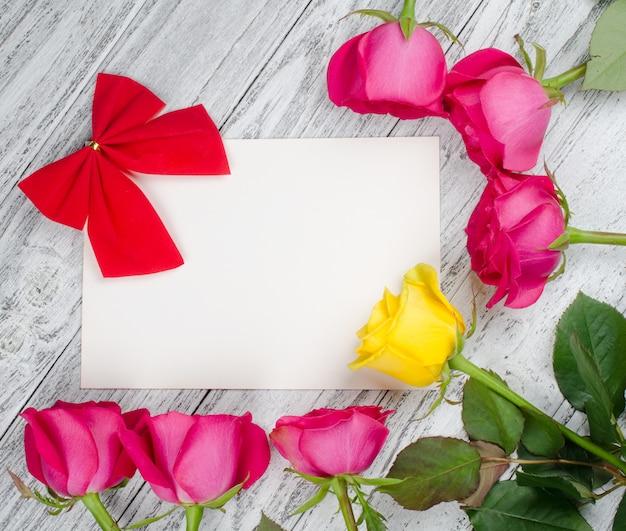 赤い弓、ピンクのバラ、空白の白いグリーティングカードに単一の黄色いバラ