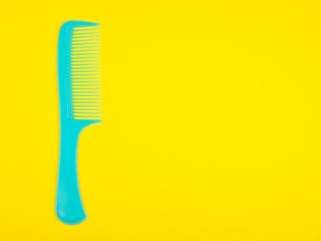 Синяя расческа для волос на ярко-желтом фоне