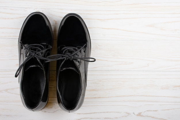 白い木製の背景に黒のパテントレザーの靴