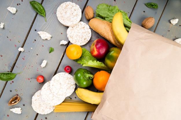 食料品の買い物のコンセプト。木製の背景の紙袋にさまざまな食品。平干し。