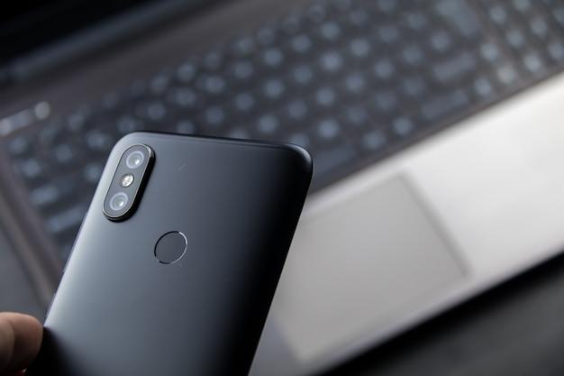 現代のノートブックとスマートフォン。デュアルカメラと指紋リーダーを搭載したモバイル