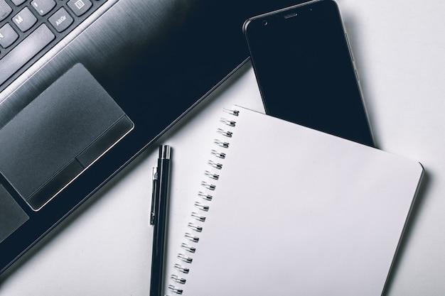 ラップトップ、スマートフォン、空白のノートブックページと白いオフィスデスク。上面図