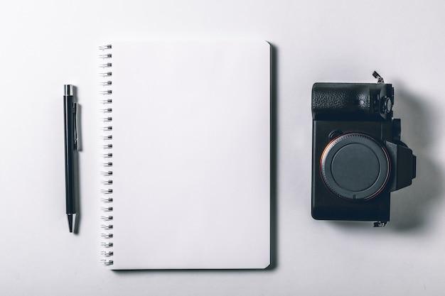ペンとデジタルカメラのミラーレスホワイトオフィスデスクテーブル。空白のノートブックページ