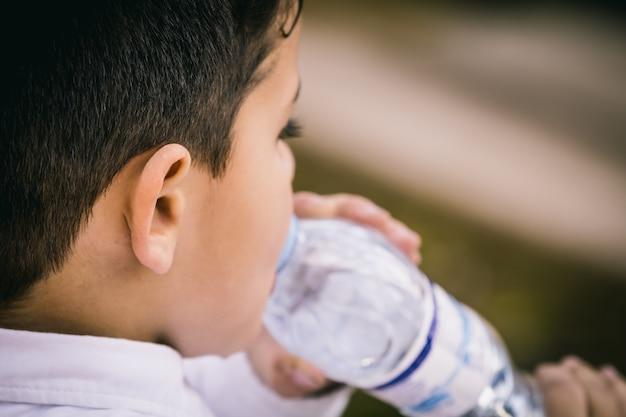 小さな男の子は水を飲む。クローズアップしてスペースをコピー