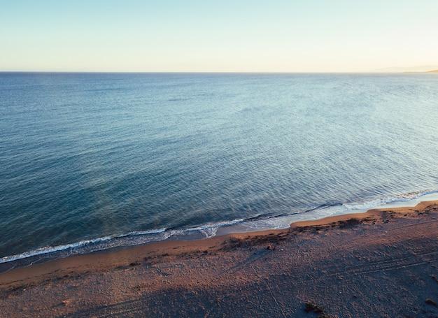 少女と日没、空撮でビーチで犬