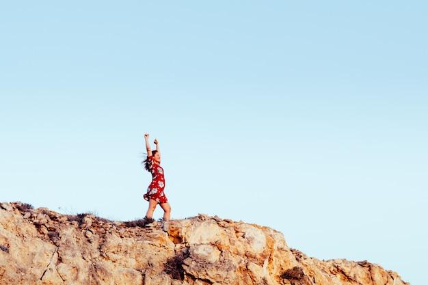 挙手と空を見ている崖の端に赤いドレスの少女