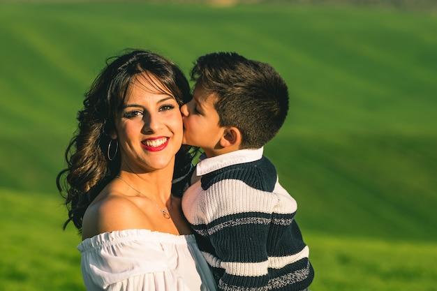 女性と夏の畑の背景の上の自然の少年。自然のポーズ