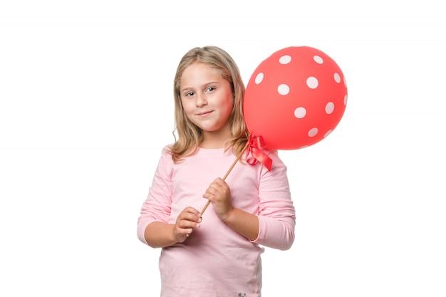 Белокурая маленькая девочка, улыбаясь в камеру с воздушным шаром на белом фоне