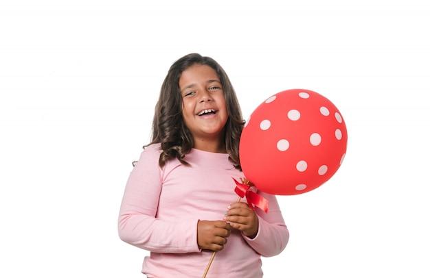 Брюнетка маленькая девочка, улыбаясь в камеру с воздушным шаром на белом фоне