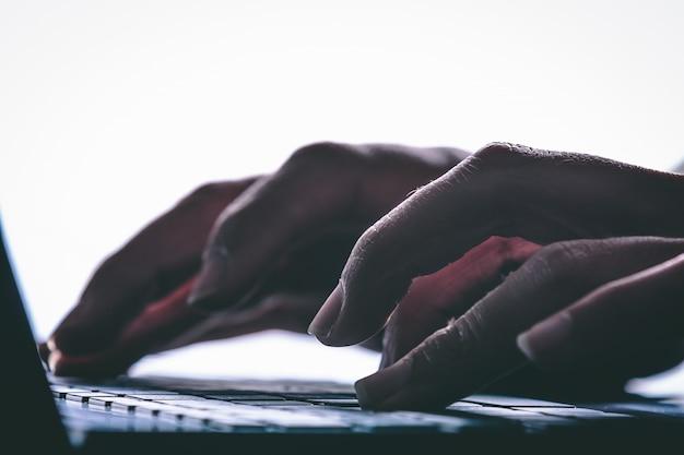 コンピューターのキーボードで入力する手。モダンスタイル