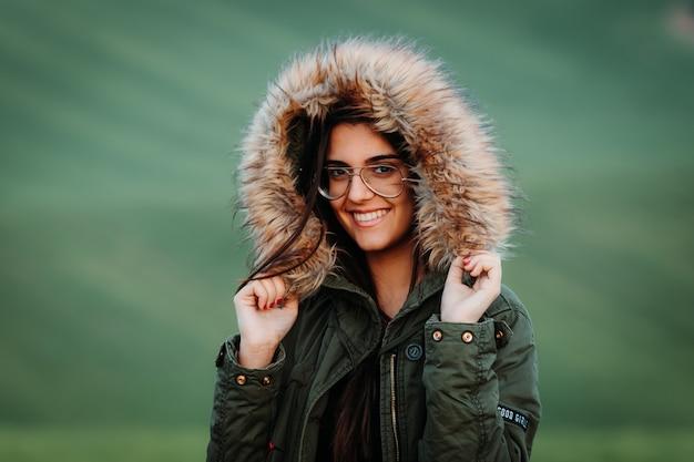 緑の牧草地で冬に寒さを感じる女性の肖像画