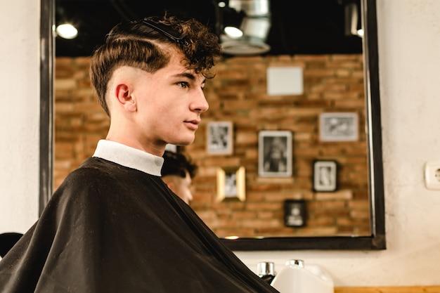 Подросток получает современную стрижку в винтажной парикмахерской