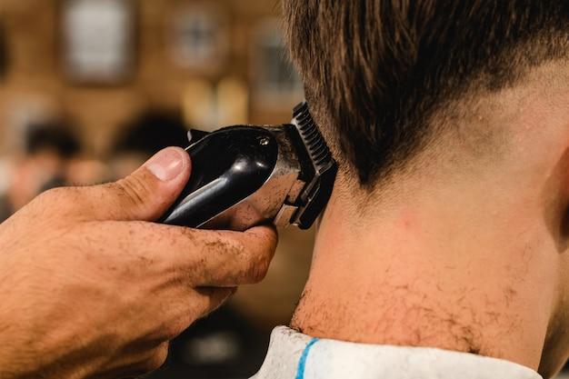 理髪店でティーンエイジャーの男の散髪を作る若いハンサムな理容室