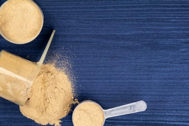 背景の青い木の上のタンパク質粉末で満たされたスクープ