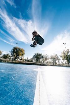 極端なスポーツ、パルクールまたはブレイクダンスと人々のコンセプト-若い男が高くジャンプ