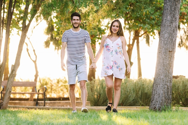 公園を歩いて、笑顔の幸せな妊娠カップル