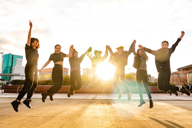 Молодые азиатские друзья, прыжки на закате. китайская команда побеждает