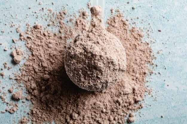 青い表面の測定用プラスチックスプーンのタンパク質粉末
