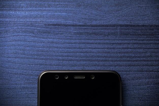 木製の背景にオフィスの机の上のスマートフォン。コピースペース。