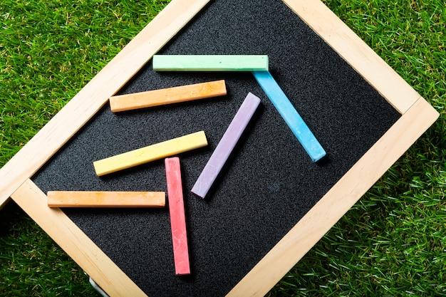 プラスチック製の草の壁にミニ黒板と色の平面図です。学校に戻るコンセプト