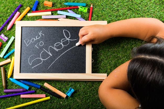 緑の芝生と黒板のハンドチョークにカラフルで鮮やかな学用品の配置に戻る