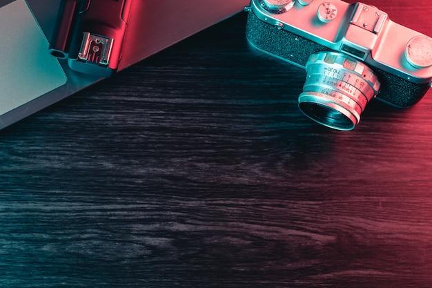 古いフィルムカメラとテーブルの上のノートパソコン。青と赤の光。コピースペース