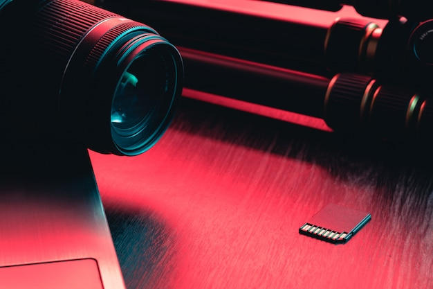 カメラのレンズ、カード、ノートパソコン、木製テーブルの上の三脚。デスクワークスペース。赤と青の光
