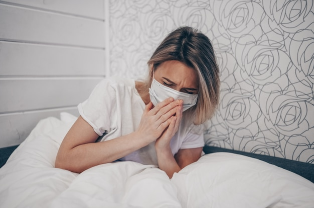 Молодая женщина, кашляющая на руках, больная коронавирусной вирусной инфекцией, распространяющей коронный вирус, покрывающий рот и нос болезненным кашлем больной пациент лежал в постели у себя дома на карантинной изоляции. первые симптомы