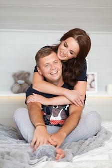美しい笑顔幸せなカップルを抱き締めると白いインテリアでお互いを見て