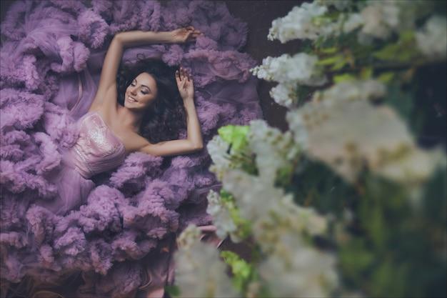 床に横たわっている豪華な長いピンクのロマンチックなドレスのファッション女性の創造的な肖像画。上面図