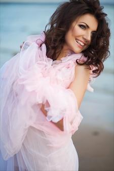 サンセットオーシャンビーチを歩いて静かな休暇の楽園の女性。ピンクのロマンチックなドレスで興奮した少女の笑顔