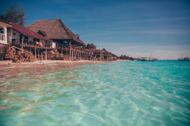 楽園の熱帯のビーチに古い木製の熱帯バンガロー