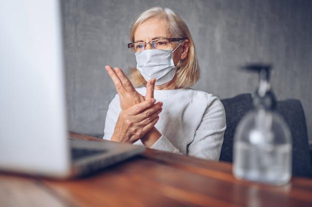 Одинокая грустная пожилая старшая женщина в медицинской маске на лице с помощью антибактериального жидкого дезинфицирующего средства для рук с портативным компьютером в домашних условиях. остаться дома