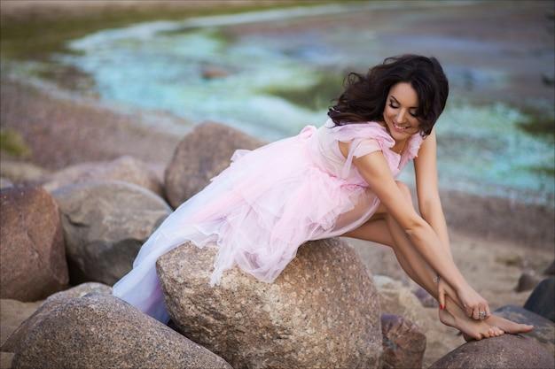 サンセットオーシャンビーチを歩いて静かな休暇の楽園の女性。豪華な熱帯の夏の休暇でリラックスしたピンクのロマンチックなドレスの女の子。