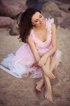 Мирный отдых рай женщина ходить на закате океан пляж. девушка в розовом платье романтическое расслабляющий на роскошный тропический летний отдых.