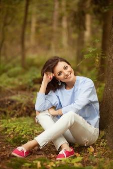 秋の公園で美しい笑顔の若い女性