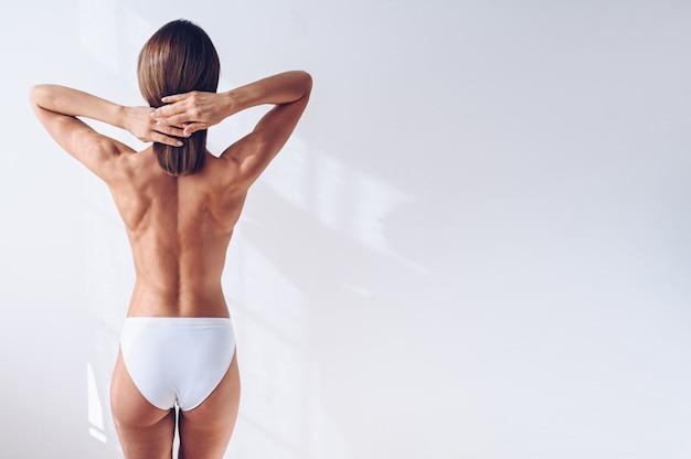 分離した白い壁に白いランジェリーで認識できないフィット女性。筋肉のスリムな魅力的な女性の背面図。テキストのスペースをコピーします。ボディケア、健康的でスポーティな生活、ヨガ、脱毛のコンセプト