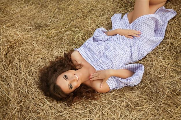 田舎の干し草ベールの上に横たわる美しい少女。