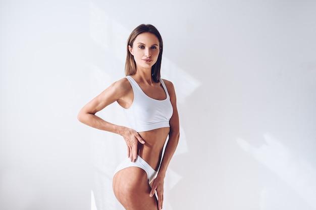 分離した白い壁に白いランジェリーの若いフィット女性。平らな腹を持つ筋肉のスリムな魅力的な女性。テキストのスペースをコピーします。ボディケア、健康的でスポーティな生活、脱毛、ヨガのコンセプト