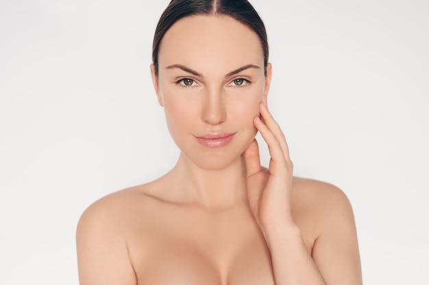 完璧な肌と髪の孤立した白い壁の美しい半分裸の自然の美しさの女性の肖像画を閉じます。ヘルスケア治療のクリーニング。スキンケアスパのコンセプトです。